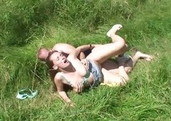 A busty woman is outside, naked and on the grass, getting fucked