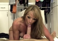 A blonde with visible pale tan lines is sucking a really large pecker