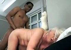 Gorgeous GILF sucking a black guy's meaty boner on a bed