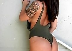 Tatted-up brunette with a one-piece bodysuit gets fucked